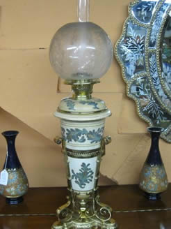 A victorian brass and pottery lamp