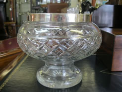 A silver rimmed cut glass bowl