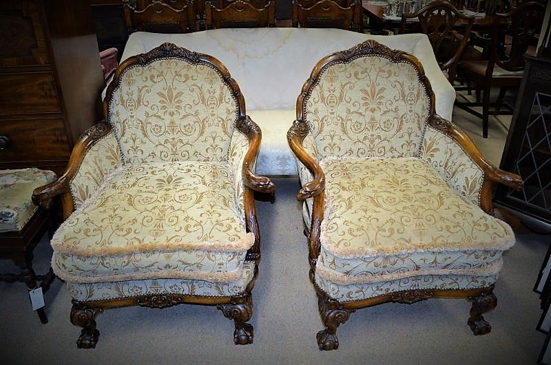 Pair of mahogany armchairs with  carved arms an sitting on ball& claw feet.